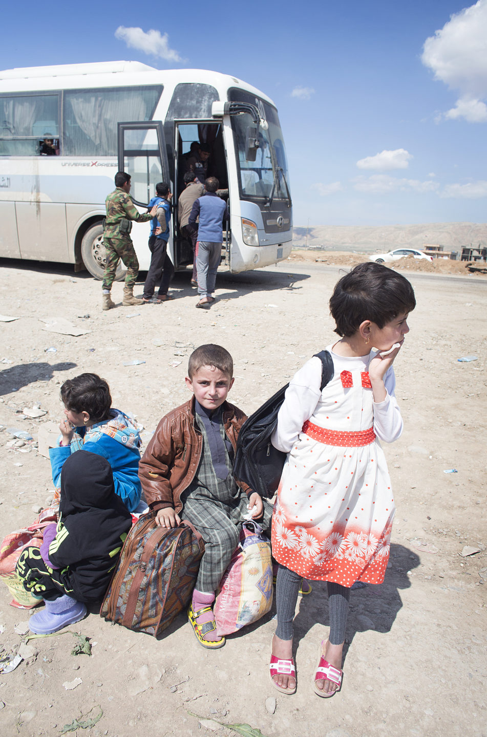 Saad Nashaf, 7, whose mother Jinan Ali was killed in an airstrike in Mosul, waits for a bus to transport his family to a safe camp in Iraqi Kurdistan.
