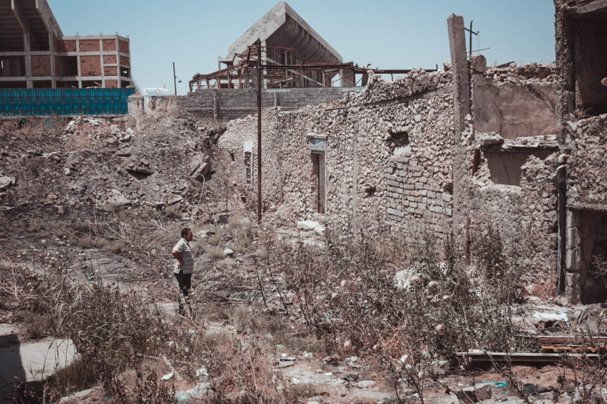 Muhammed looks at a ruined house
