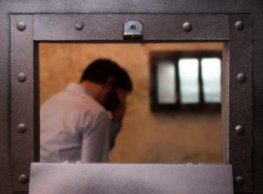 Prisoner in a cell behind a door